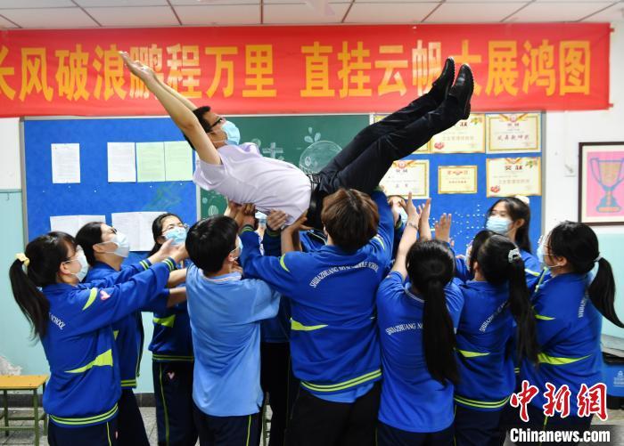 图为同学们将老师举高抛起,表达着自己对老师的感谢之情。 翟羽佳 摄