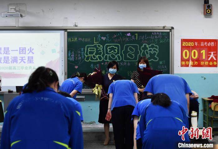 图为同学们向教授他们知识的老师鲜花,并深深的鞠躬。 翟羽佳 摄