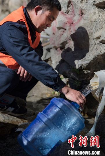4月26日,在西藏自治区林芝市朗县,张富强在距离临电管理所20公里外的地方接取山泉水。由于山上用水不便,他们一周要来接一次泉水。 焦宏涛 摄