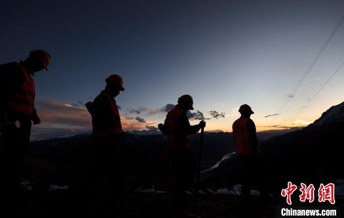 4月25日,在西藏自治区林芝市朗县,中铁电气化局集团的巡线小分队踏着夕阳结束一天的巡线后下山途中。 焦宏涛 摄