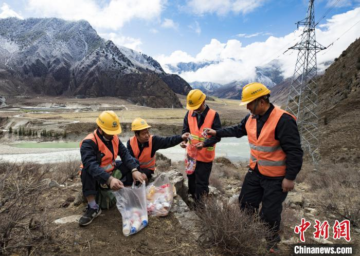 4月25日,在西藏自治区林芝市朗县,中铁电气化局集团的巡线小分队员们正在把用餐后的生活垃圾装袋带走。 焦宏涛 摄