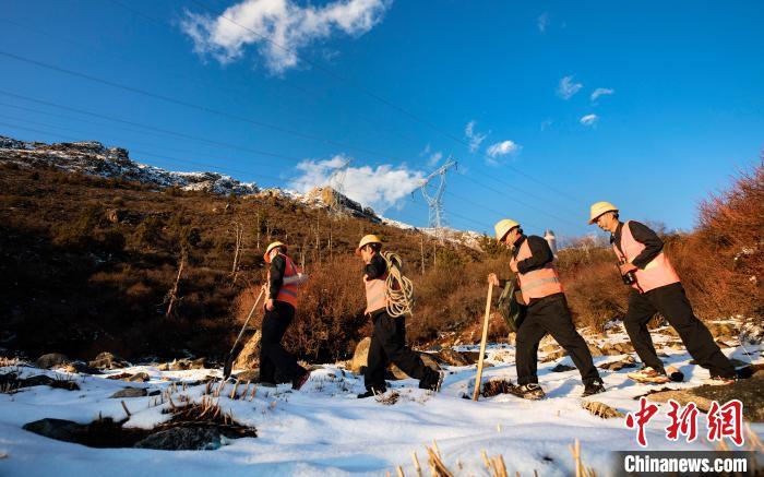4月25日,在西藏自治区林芝市朗县,中铁电气化局集团的巡线小分队踏着积雪在拉嘎山上海拔4300米的地方巡查线路。 焦宏涛 摄