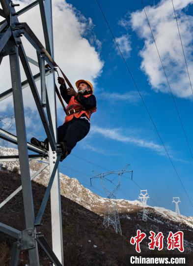 4月25日,在西藏自治区林芝市朗县,中铁电气化局集团的巡线员张富强在海拔4300米处登上供电铁塔检查。 焦宏涛 摄