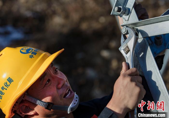 4月25日,在西藏自治区林芝市朗县,中铁电气化局集团的巡线员张富强在巡查中发现供电铁塔的螺丝松动,立即进行紧固。 焦宏涛 摄