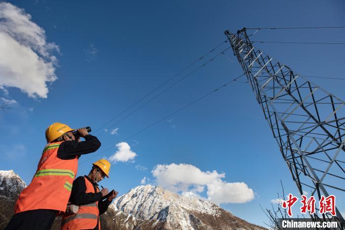 4月25日,在西藏自治区林芝市朗县,中铁电气化局集团的巡线员马有军(左)和高飞(右)在拉嘎山上海拔4300米的地方用望远镜观察线路情况。 焦宏涛 摄