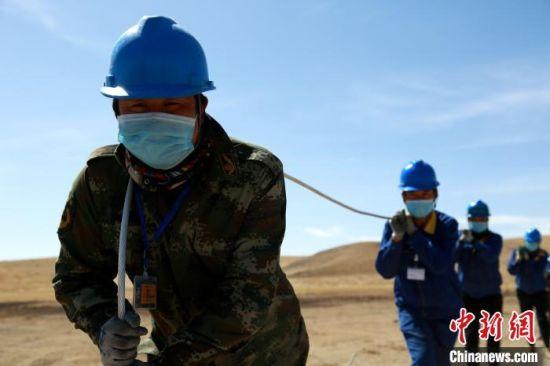 图为施工人员们正在立杆、放线、紧线。 韩文静 摄