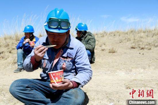 图为施工人员们席地而坐,手里端着热气腾腾的盒饭。 韩文静 摄
