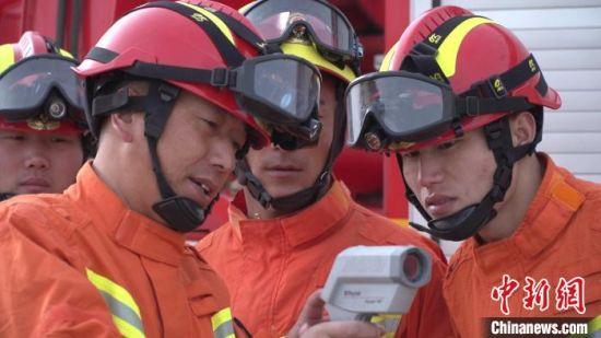 图为巴才洛与消防人员探讨业务。(资料图) 赵智彬 摄