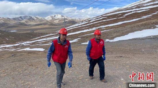 图为在青海省玉树藏族自治州曲麻莱县秋智乡附近,扎西达杰(右一)和队友一起观察路况,确保后方骡马队安全行进。 徐晓韬 摄