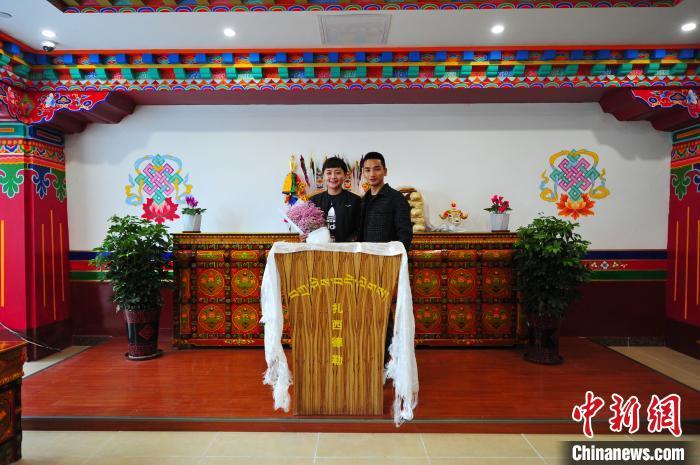 图为拉萨市民旦增洛桑(右)和次仁卓嘎办理完结婚登记手续合影留念。 张伟 摄