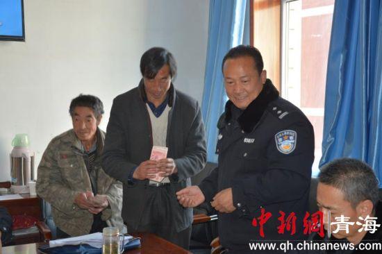 图为贵南县公安局民警为农民工发放拖欠的工资。贵南县公安局供图