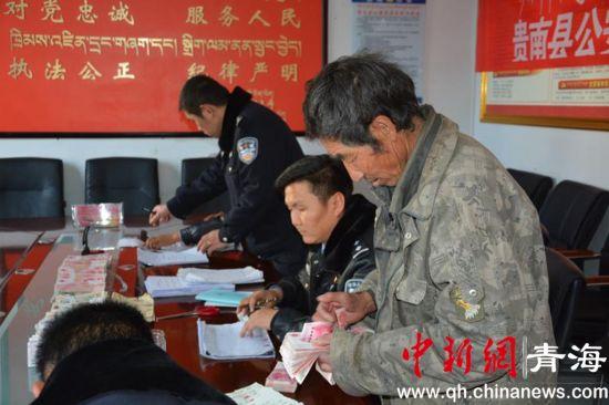 图为领到工资的农民工正在数钱。贵南县公安局供图